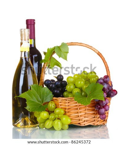 Ripe red grapes and wine in basket isolated on white - stock photo