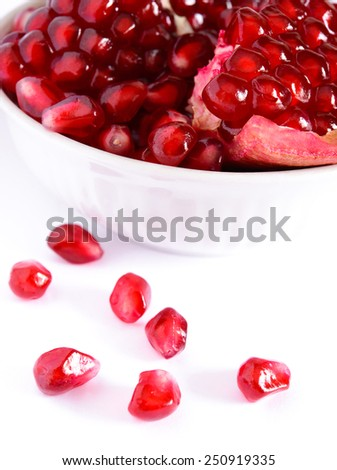 Ripe Red Pomegranate Seeds in the White Plate on the White Background - stock photo