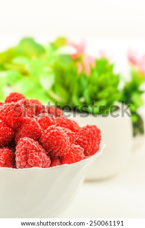 Ripe red raspberries in glass dish and is scattered on table. - stock photo