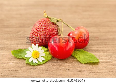 Ripe red strawberries, cherries and small daisy flowers on a wooden background. Strawberries over wooden table background with copy spac - stock photo