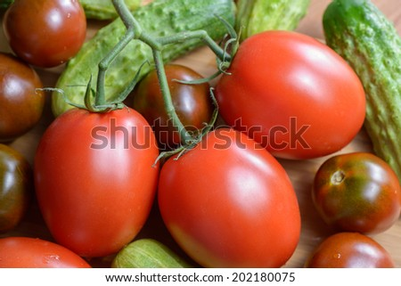 Ripe red tomatoes and cucumbers on the plate is brightly lit close up