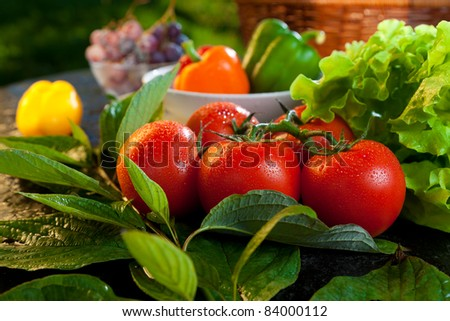 Ripe red tomatoes on the table in a country house - stock photo