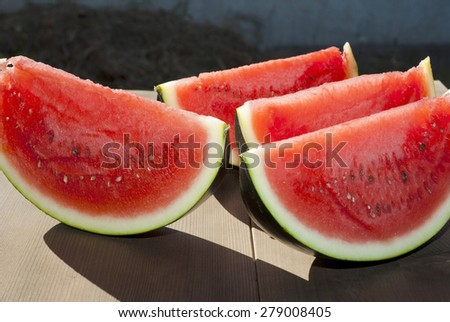 ripe red watermelon portions on wooden table - stock photo