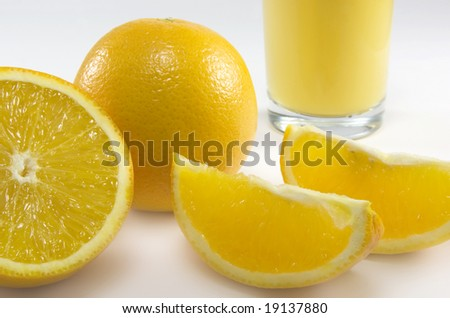 ripe sliced oranges with a glass filled with juice