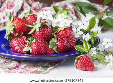 Ripe strawberries decorated with fresh flowers cherries, on wooden table. Selective focus - stock photo