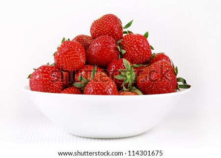 Ripe strawberries in a porcelain plate side view. - stock photo