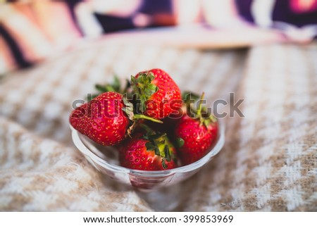 Ripe strawberries in a vase of glass on the plaid - stock photo