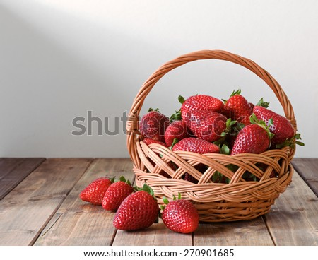 ripe strawberries in a wicker basket on a wooden table - stock photo
