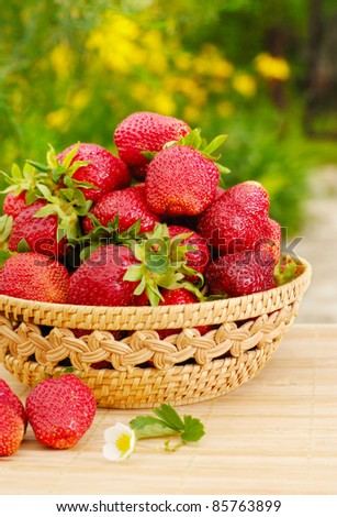 Ripe strawberries in the basket on the green background - stock photo