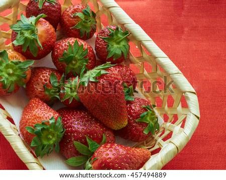 ripe strawberries in wicker basket on a red napkin - stock photo