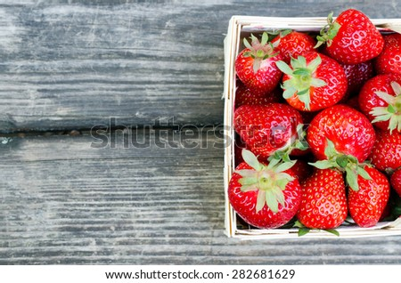 Ripe strawberries in wooden box over wooden table - stock photo