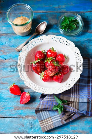 ripe strawberries on the plate with mint on blue rustic table - stock photo