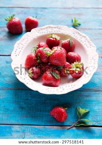 ripe strawberries on the plate with mint on blue rustic table