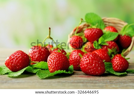 Ripe strawberries with leaves in wicker basket on wooden table on blurred background - stock photo