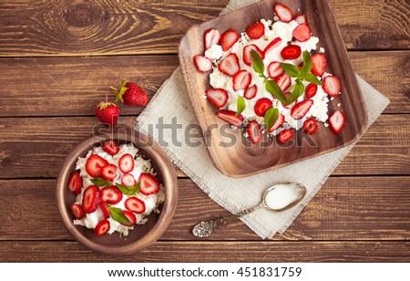 Ripe strawberry and cottage cheese. Farmer products. Food composition on a wooden background. Top view - stock photo