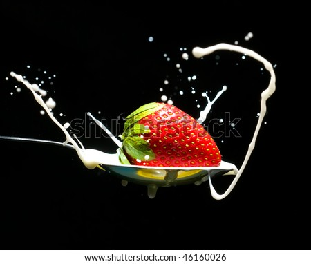 ripe strawberry drops in a spoonful of cream on a black background - stock photo