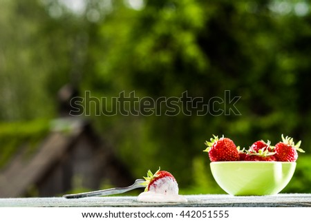 Ripe strawberry in a bowl with sour cream on wooden table on blurred foliage background. - stock photo