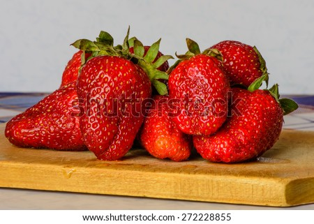 Ripe strawberry on a cutting Board on the kitchen table. - stock photo