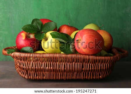 Ripe sweet apples with leaves in basket on wooden background - stock photo
