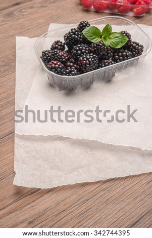 Ripe sweet blackberries and raspberries on wood table background - stock photo
