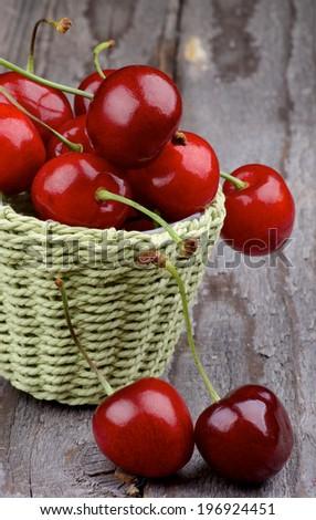 Ripe Sweet Cherries in Green Wicker Basket closeup on Rustic Wooden background - stock photo