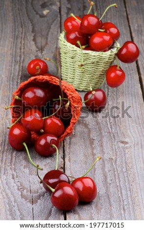 Ripe Sweet Cherries in Two Wicker Baskets closeup on Rustic Wooden background - stock photo