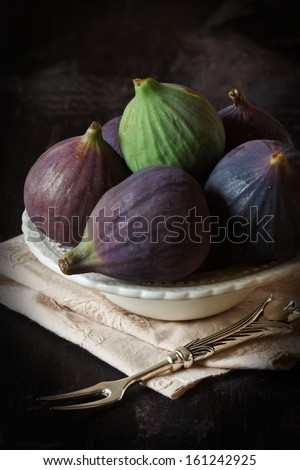 Ripe sweet figs in a bowl on a dark background. - stock photo