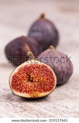 Ripe sweet figs on white wooden background