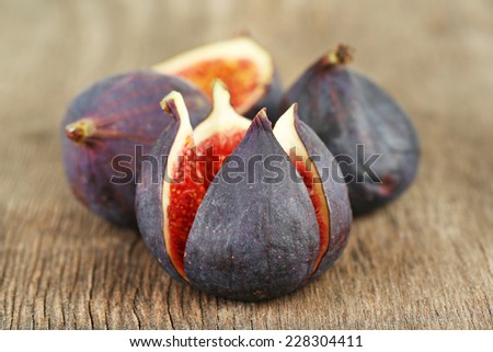 Ripe sweet figs on wooden background - stock photo