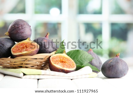 Ripe sweet figs with leaves in basket, on wooden table, on window background - stock photo