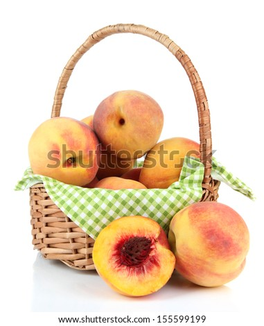 Ripe sweet peaches in wicker basket, isolated on white - stock photo
