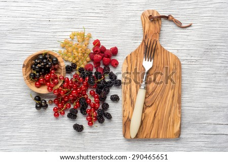 Ripe Sweet Raspberries, currant, mulberry, red and yellow currant   on the Wooden Table Against the wooden background. Summer Berries - stock photo