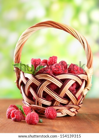 Ripe sweet raspberries in basket on wooden table, on green background