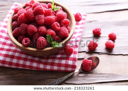 Ripe sweet raspberries in bowl on table close-up - stock photo