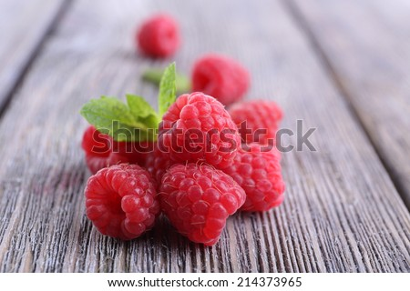Ripe sweet raspberries on table close-up - stock photo