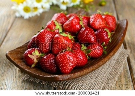 Ripe sweet strawberries on plate on table close-up - stock photo