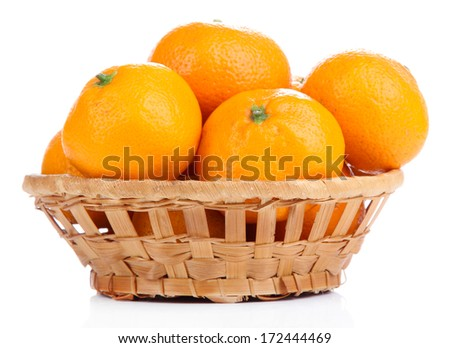 Ripe sweet tangerines in wicker basket, isolated on white - stock photo
