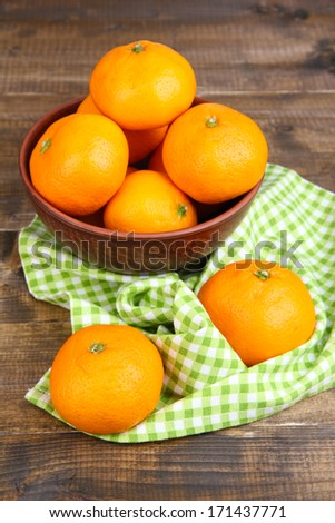 Ripe sweet tangerines with spices in bowl, on napkin, on wooden background