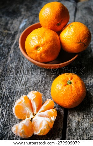Ripe tangerine fruit and basket full of mandarines on wooden background - stock photo