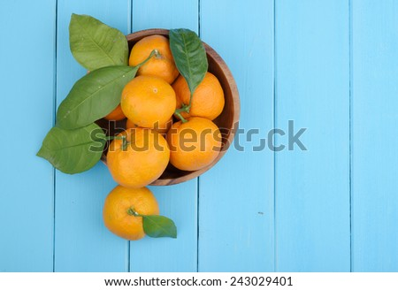 ripe tangerine with green leaves in a wooden bowl on the table - stock photo