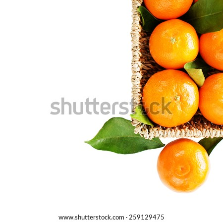 Ripe tangerine with leaves in a basket, isolated on white - stock photo