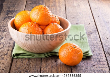 Ripe tangerines in a bowl on a wooden table  - stock photo