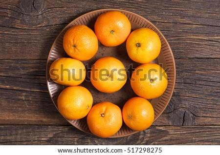 Ripe tangerines in plate on old wooden table, top view