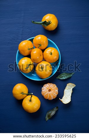 Ripe tangerines over dark blue wooden background, above view - stock photo