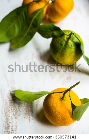 Ripe tangerines with green leaves on dark rustic background