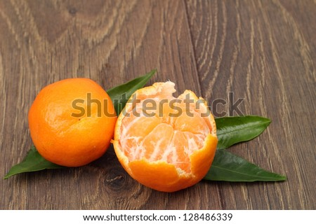 Ripe tangerines with leaves on dark wood background/Mandarin