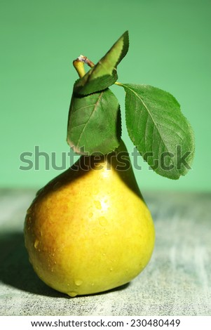 Ripe tasty pear, on wooden table - stock photo
