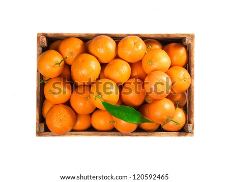 Ripe tasty tangerines with fresh leaves in wooden box isolated on white, top view - stock photo