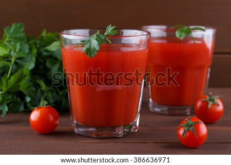 Ripe tomato and juice with parsley on brown wooden background