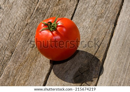 ripe tomato on a wooden table - stock photo